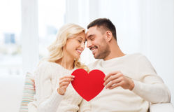 Happy couple with red heart hugging at home Stock Photography