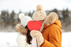 Happy couple with red heart over winter landscape. People, season, love, christmas and valentines day concept - happy couple hiding faces behind blank red heart Royalty Free Stock Image