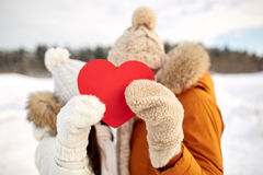 Happy couple with red heart over winter landscape. People, season, love, christmas and valentines day concept - happy couple hiding faces behind blank red heart Royalty Free Stock Photo
