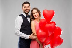 Happy couple with red heart shaped balloons stock images