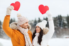 Happy couple with red hearts over winter landscape Stock Photo
