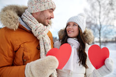 Happy couple with red hearts over winter landscape Royalty Free Stock Image