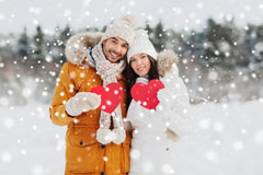 Happy couple with red hearts over winter landscape Royalty Free Stock Photos