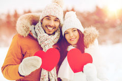 Happy couple with red hearts over winter landscape Royalty Free Stock Images
