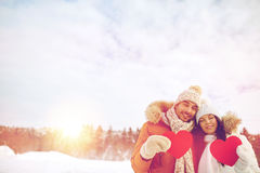 Happy couple with red hearts over winter landscape Royalty Free Stock Photography