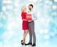 Happy couple with red sale sign Royalty Free Stock Photography