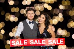 Happy couple with red sale sign. Shopping, people and black friday concept - happy couple with red sale sign over night lights background Royalty Free Stock Photos