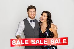 Happy couple with red sale sign. Shopping, people and fashion concept - happy couple with red sale sign Royalty Free Stock Images
