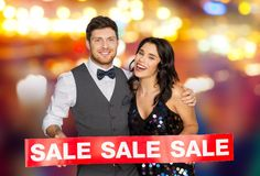 Happy couple with red sale sign. Shopping, people and fashion concept - happy couple with red sale sign over night city lights background Stock Photo