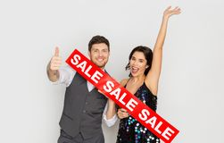 Happy couple with red sale sign showing thumbs up. Shopping, people and fashion concept - happy couple with red sale sign showing thumbs up Royalty Free Stock Photography