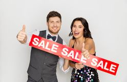 Happy couple with red sale sign showing thumbs up. Shopping, people and fashion concept - happy couple with red sale sign showing thumbs up Stock Image