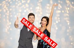 Happy couple with red sale sign showing thumbs up. Shopping, people and fashion concept - happy couple with red sale sign showing thumbs up over festive lights Royalty Free Stock Image