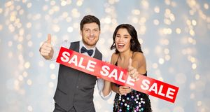 Happy couple with red sale sign showing thumbs up. Shopping, people and fashion concept - happy couple with red sale sign showing thumbs up over festive lights Stock Photo