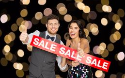 Happy couple with red sale sign showing thumbs up. Shopping, people and fashion concept - happy couple with red sale sign showing thumbs up over lights on black Stock Photography
