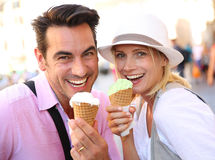 Happy couple refreshing with ice cream on sunny day. Cheerful couple in Rome eating ice cream cones Stock Images