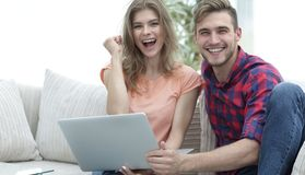 Young couple rejoices,sitting on the couch in front of the open laptop. Happy couple rejoices,sitting on the couch in front of the open laptop Royalty Free Stock Photos