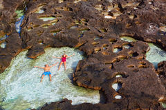 Happy couple relax in natural sea pool at Angel�s Billabong stock photography