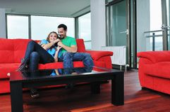Happy couple relax on red sofa Royalty Free Stock Image