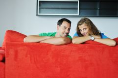 Happy couple relax on red sofa Royalty Free Stock Photo