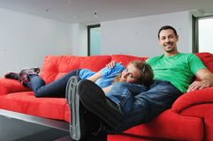 Happy couple relax on red sofa Stock Photos