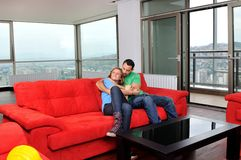 Happy couple relax on red sofa Royalty Free Stock Photography
