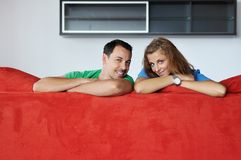Happy couple relax on red sofa Royalty Free Stock Images