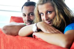 Happy couple relax on red sofa Royalty Free Stock Photos