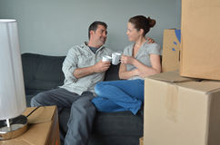 Happy couple relax on a sofa during a move into a new home. Happy couple men (age 40-45) and a women (age 30-35) relax on a sofa during a move into a new home Royalty Free Stock Image