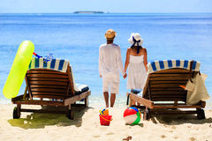 Happy couple relax on a tropical sand beach. Happy loving couple relax on a tropical sand beach Royalty Free Stock Images