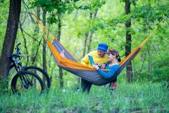 Happy couple relaxes and uses tablet pc in a hammock. In the forest after riding a bikes on a awesome sunny day - wonderful weekend in nature Stock Image