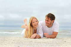Happy Couple Relaxing on the Beach by the Ocean Royalty Free Stock Photo