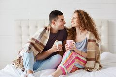 Happy couple relaxing in bed with hot beverage, holds cups full of tea or coffee, sit under warm blanket, dresses casually, stock photos