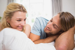 Happy couple relaxing on bed smiling at each other Royalty Free Stock Photography