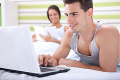 Happy couple relaxing in bed Stock Images