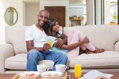 Happy couple relaxing on the couch with breakfast Stock Photos