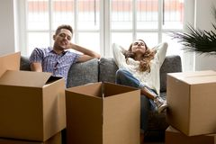Happy couple relaxing on couch after moving in new home. Smiling young husband and wife homeowners or tenants taking break for rest together while packing Stock Image