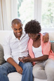 Happy couple relaxing on the couch with smartphone Royalty Free Stock Photography