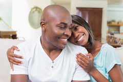 Happy couple relaxing on the couch smiling at each other Royalty Free Stock Photography