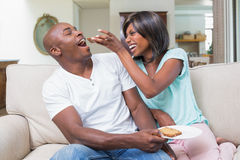 Happy couple relaxing on the couch with toast Royalty Free Stock Images