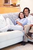 Happy couple relaxing on the couch together Royalty Free Stock Photography