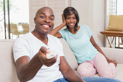 Happy couple relaxing on the couch watching tv Stock Photography