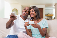 Happy couple relaxing on the couch watching tv Stock Images