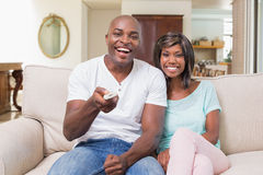 Happy couple relaxing on the couch watching tv Royalty Free Stock Photos