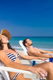 Happy couple relaxing on deck chair at the beach Royalty Free Stock Images