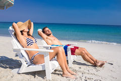 Happy couple relaxing on deck chair at the beach Stock Image