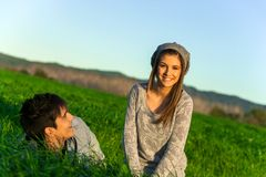 Happy couple relaxing in grass field. Royalty Free Stock Image