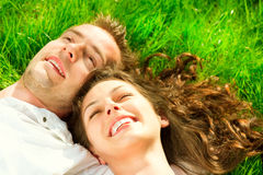 Happy couple relaxing on green grass Royalty Free Stock Photos