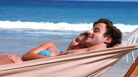 Happy couple relaxing in hammock on beach. In ultra hd format stock footage