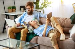 Happy couple relaxing at home with laptop and tablet. Happy family couple relaxing at home with laptop and tablet royalty free stock photos