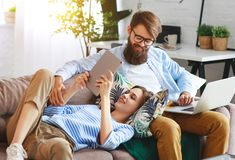 Happy couple relaxing at home with laptop and tablet stock image